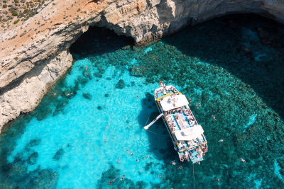 People using the slide from a boat and swimming at the Blue Lagoon, Comino